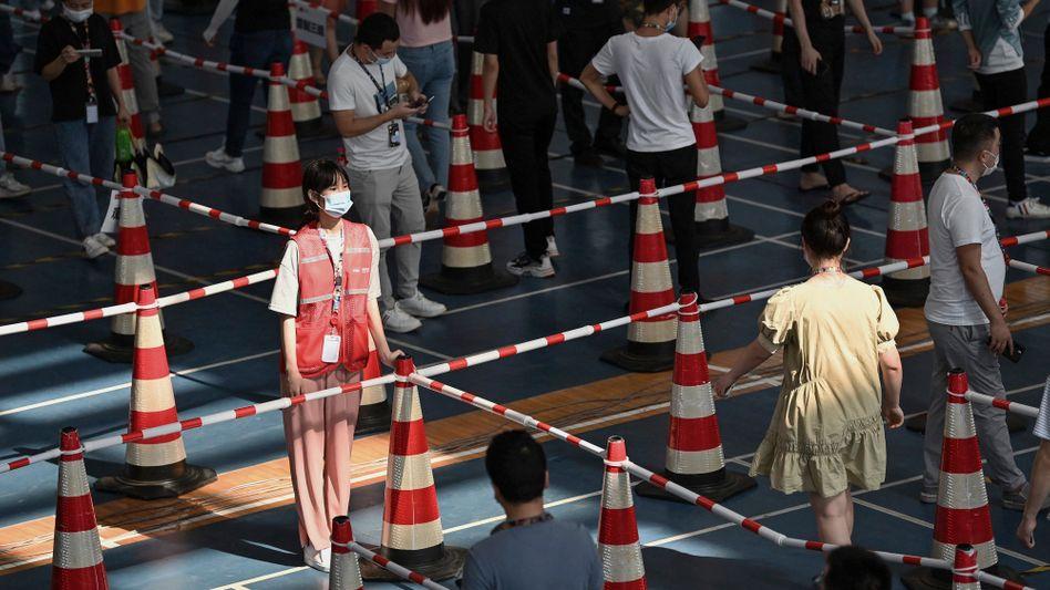 Helferin bei einem Massentest Anfang August in einer Turnhalle in Wuhan: Drei Infektionen führen zu Millionen Abstrichen