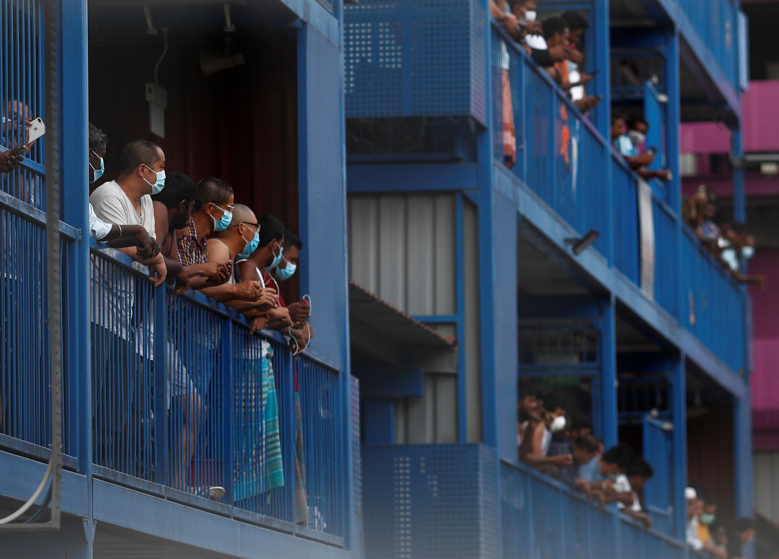 Workers from Bangladesh, India and China look out of their balconies during food distribution at Punggol S-11 workers' dormitory, which was gazetted to be an isolation facility after it became a cluster of coronavirus cases (COVID-19), in Singapore