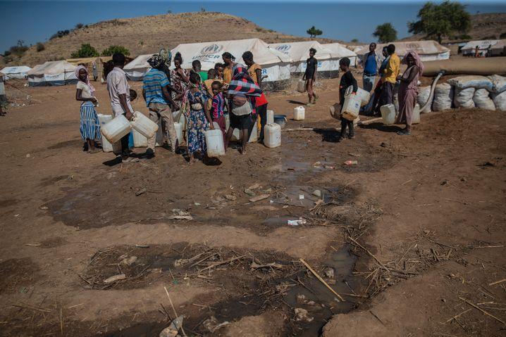 Geflüchtete aus Tigray warten im Sudan auf Wasser: Millionen Menschen sind auf Nahrungsmittelhilfen angewiesen. Doch die Hilfsorganisationen erreichen nur wenige Zehntausend.