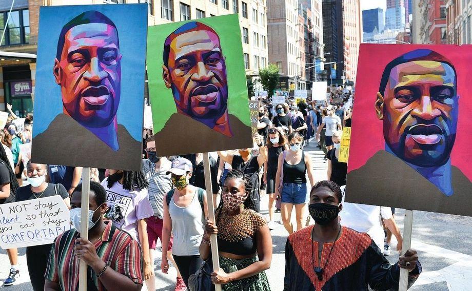 In New York gehen am 19. Juni viele Menschen auf die Straße. Auf manchen Protest-Schildern ist das Gesicht von George Floyd zu sehen.