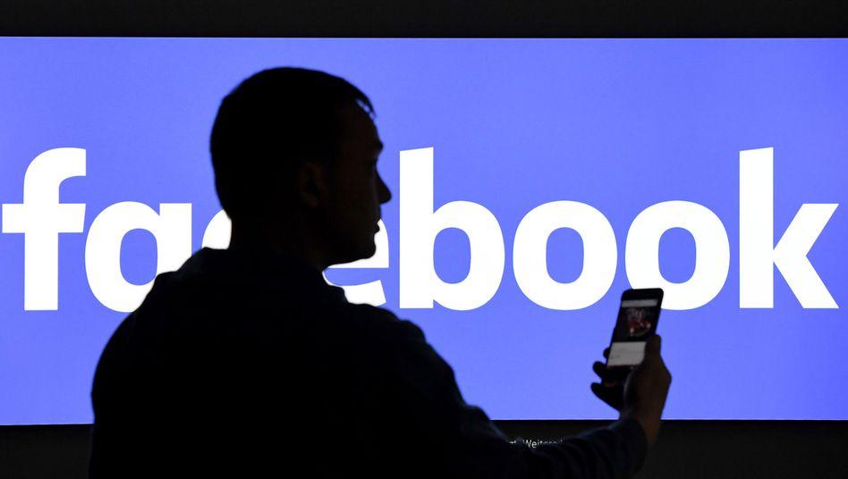 Ein Mann mit einem Smartphone steht vor dem Facebook-Logo