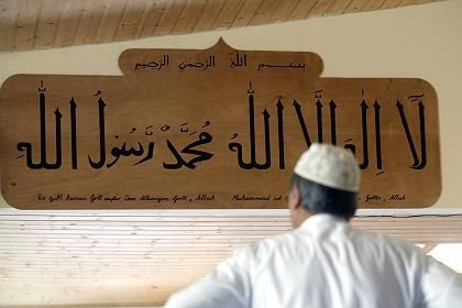 """A member of the Ahmadiyya Muslim community in Berlin stands in front of a sign that reads, """"There is no God but Allah."""" The community has just won approval for a new mosque in an eastern district of the German capital."""