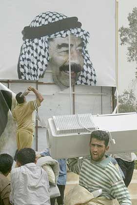 Plündern ist harte Arbeit: Während seine Landsleute auf ein Saddam-Bild einschlagen, macht sich ein Iraker mit einem Kühlschrank davon