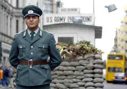 Actor Tom Luszeit dresses up as an East German police officer at Checkpoint Charlie.