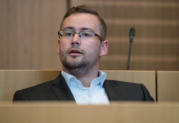 ARCHIV - Der rheinland-pfälzische AfD-Spitzenkandidat Sebastian Münzenmaier sitzt am 27.07.2017 auf der Anklagebank des Verhandlungssaales des Amtsgerichts in Mainz (Rheinland-Pfalz). Die Staatsanwaltschaft wirft dem Politiker versuchten Raub und gefährliche Körperverletzung vor. (zu dpa «Fortsetzung Prozess gegen AfD-Politiker Münzenmaier» vom 11.09.2017) Foto: Boris Roessler/dpa +++(c) dpa - Bildfunk+++   Verwendung weltweit