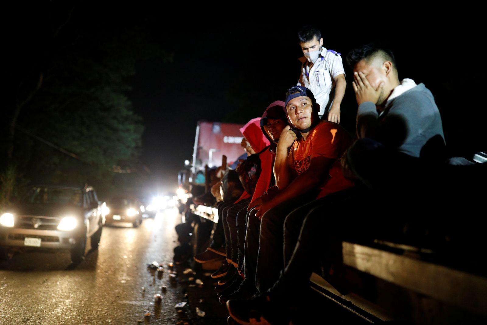 Honduran migrants trying to reach the U.S. hitchhike on a truck, through Izabal department
