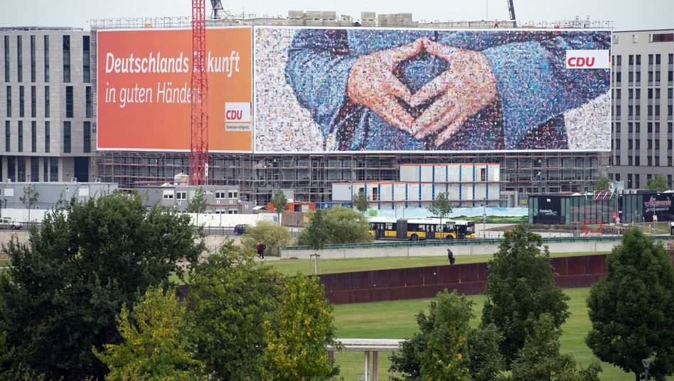The hands of power: A giant campaign poster featuring Angela Merkel's trademark diamond pose has been hung near Berlin's central station.