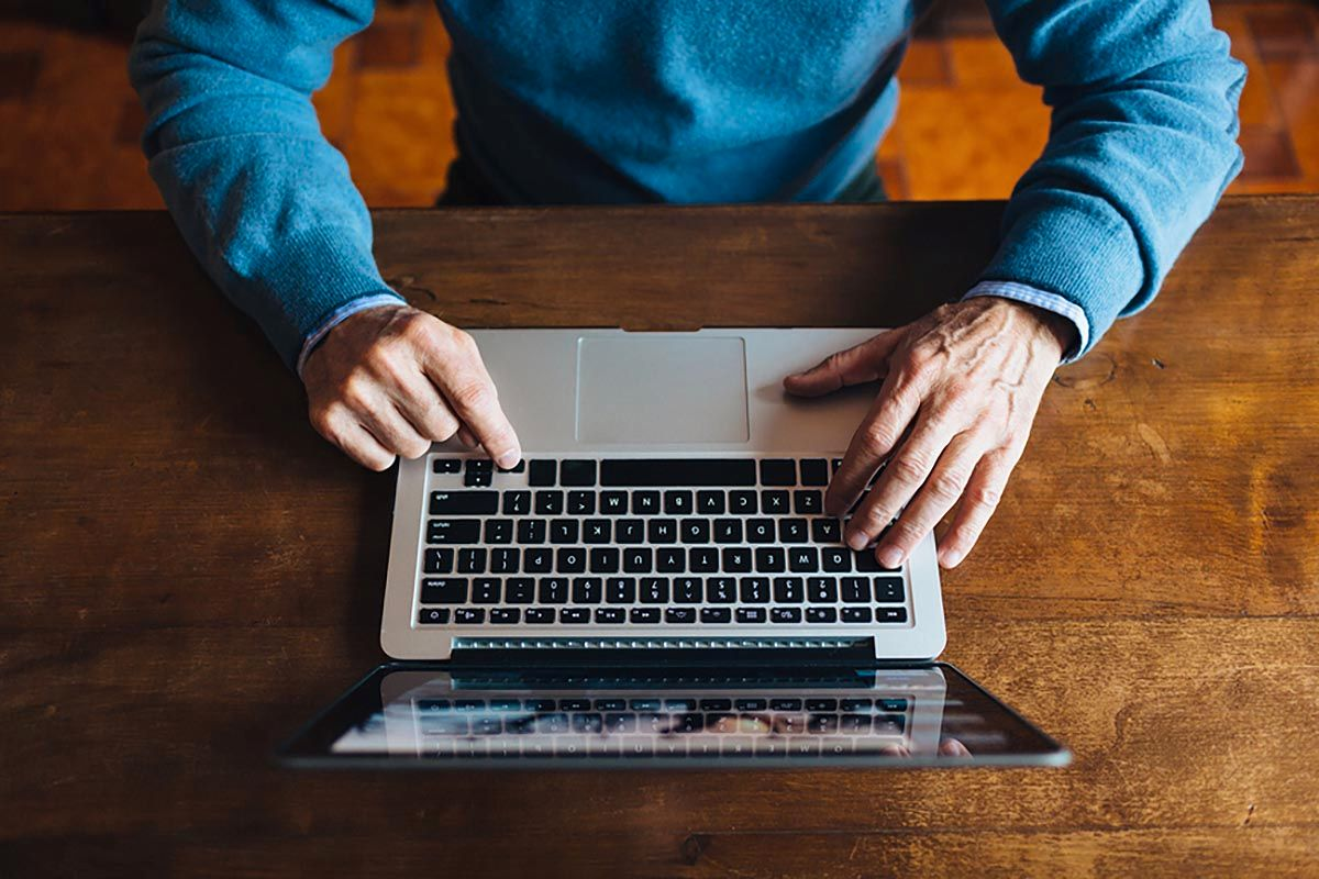 Detail Of The Hands Of Elderly Man Using Laptop