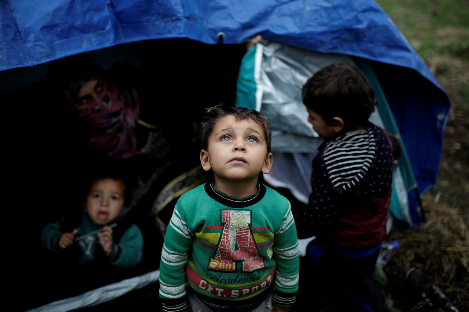 FILE PHOTO: A Syrian refugee boy stands in front of his family tent at a makeshift camp for refugees and migrants next to the Moria camp on the island of Lesbos