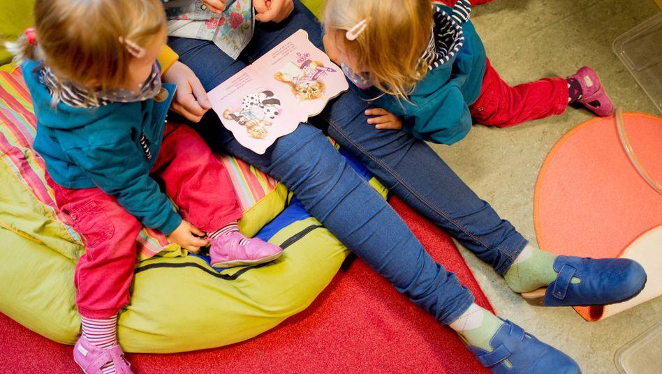 Mit Kindern über einem Buch hängen: Manche Eltern trauen sich das nicht zu (Symbolbild)