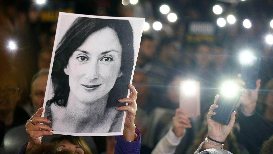 Mit einem Foto der ermordeten Journalistin fordern Menschen in Valletta den Rücktritt des Ministerpräsidenten