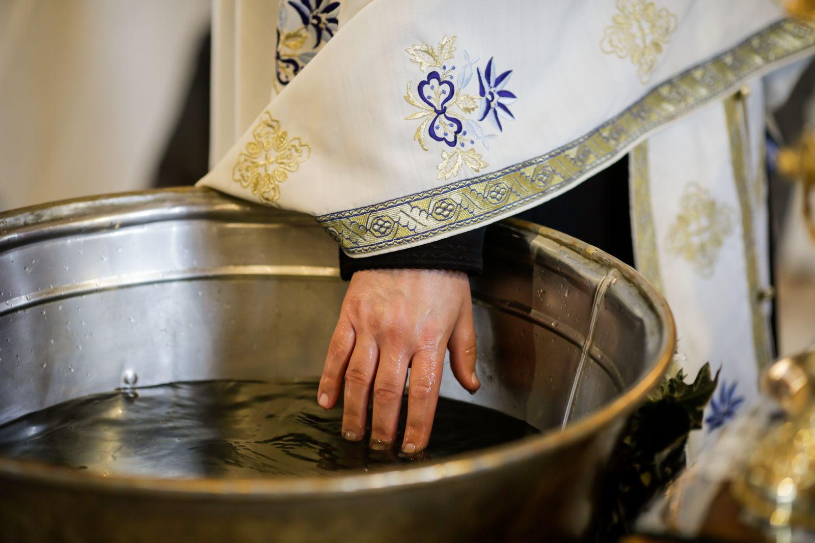 Details with the hand of an Orthodox priest testing the warmth of the water in the baptismal font.
