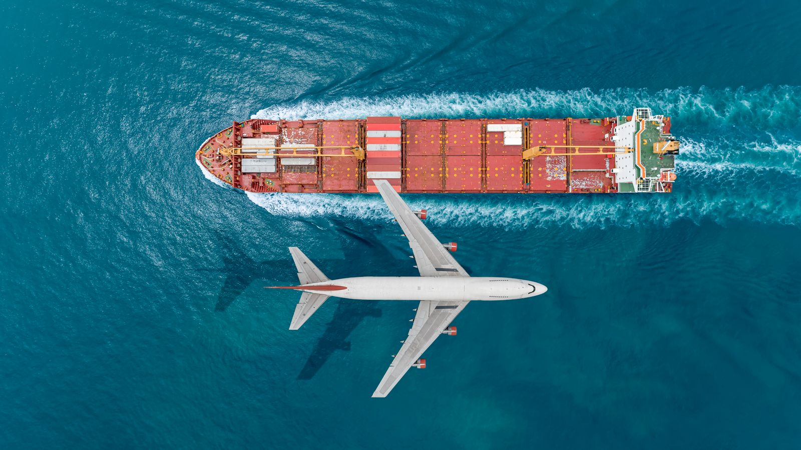 Container ship sail through airplane flying on the sea.