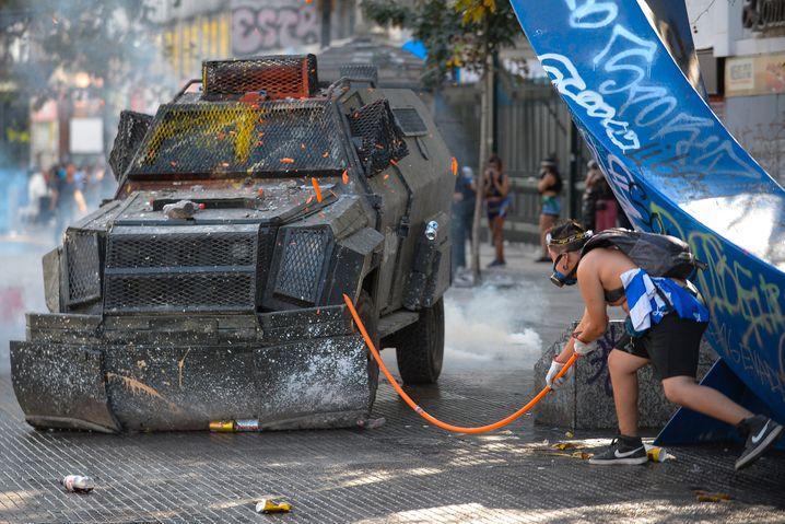 Santiago de Chile: Ein Demonstrant stellt sich einem Tränengas-Fahrzeug der Polizei entgegen