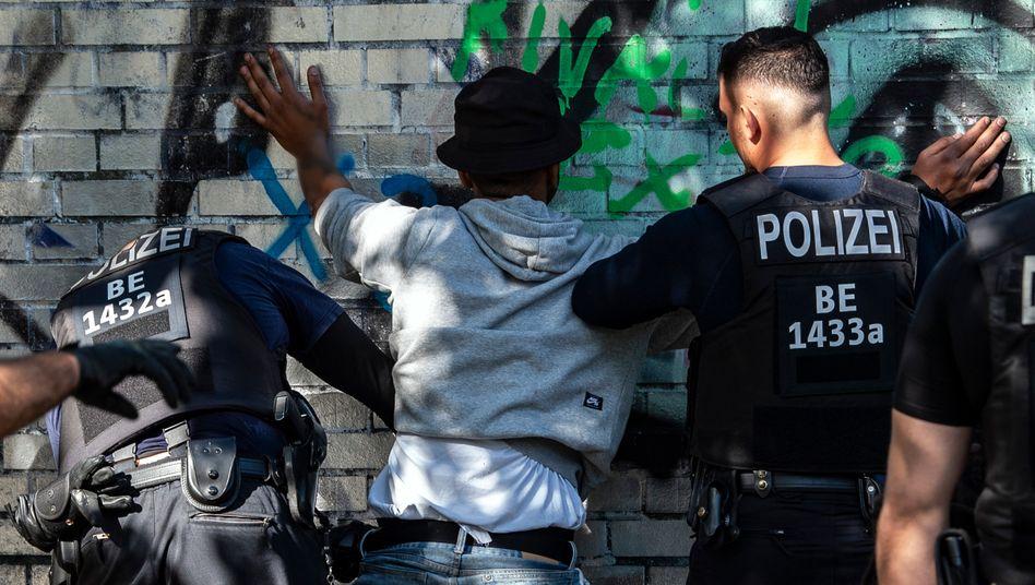 Polizisten kontrollieren einen Schwarzen als mutmaßlichen Drogendealer
