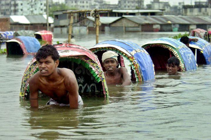 Rikschafahrer auf überfluteten Straßen in Bangladesch