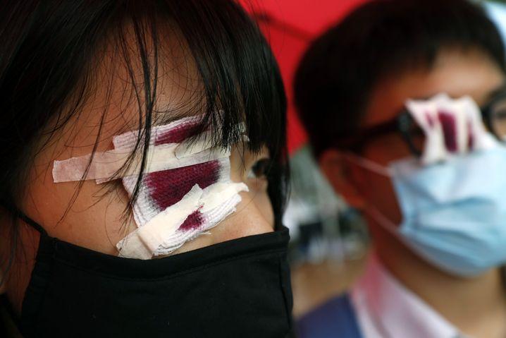 Diese Hongkonger Schüler haben sich blutrot gefärbte Kompressen aufgeklebt, in Erinnerung an eine Demonstrantin, die durch Gummigeschosse ein Auge verlor