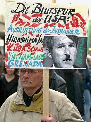 A German man carries a banner with a picture of Bush as Hitler during a 2003 demonstration against the Iraq war in Leipzig. Bush-bashing is something of a national sport in Germany.