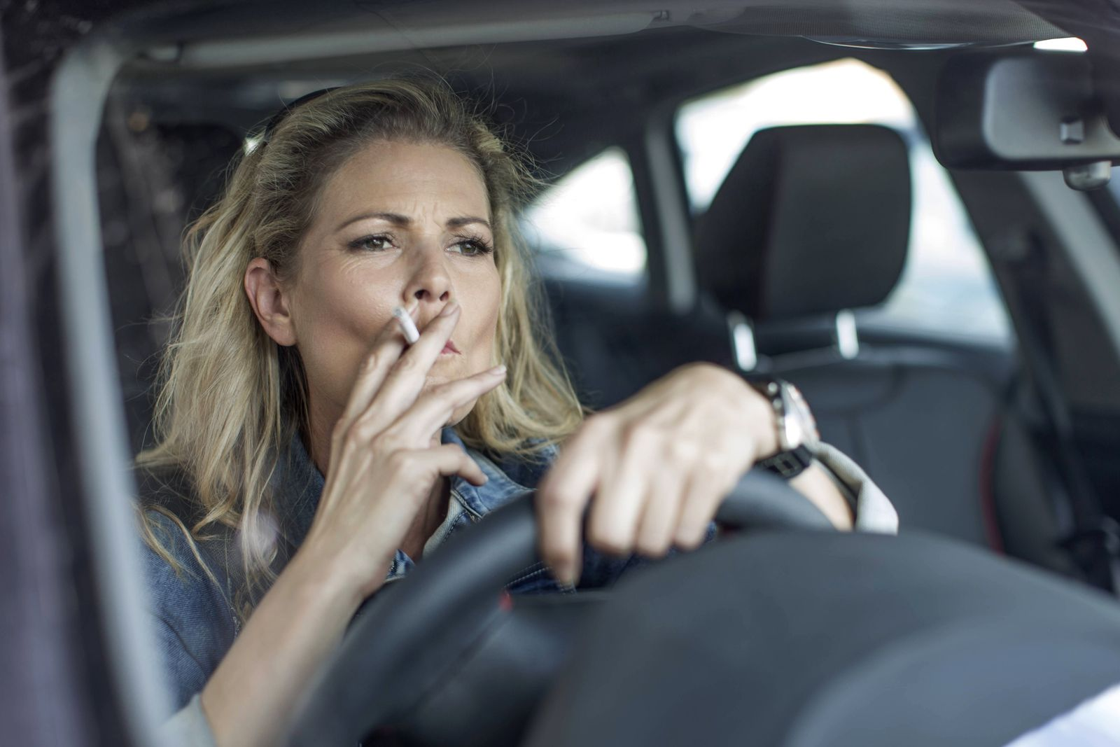 Serious woman in car smoking a cigarette model released Symbolfoto PUBLICATIONxINxGERxSUIxAUTxHUNxONLY ZEF004680