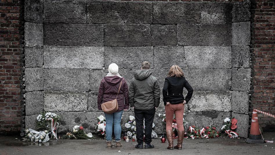 Jugendliche Besucher in der Gedenkstätte Auschwitz: An der »Todeswand« im Stammlager, im Hof zwischen Block 10 und Block 11, wurden Häftlinge erschossen