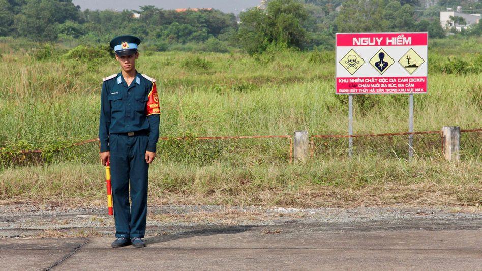 Ein vietnamesischer Soldat steht neben einem Schild, das vor dem Gift warnen soll