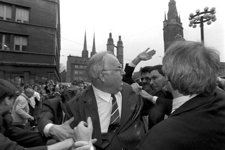 Der Eierwurf von Halle: Nachdem Kohl am 10. Mai 1991 vor dem Stadthaus in Halle von einem Demonstranten mit Eiern beworfen worden ist, versucht er sich in Rage einen Weg durch die Menge zu bahnen, um den Täter ausfindig zu machen.