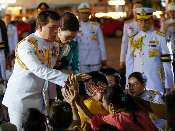 König Rama X. und seine Frau Königin Suthida mit ihren Anhängern in Bangkok: Gegebenenfalls Aufenthaltsgenehmigung entziehen
