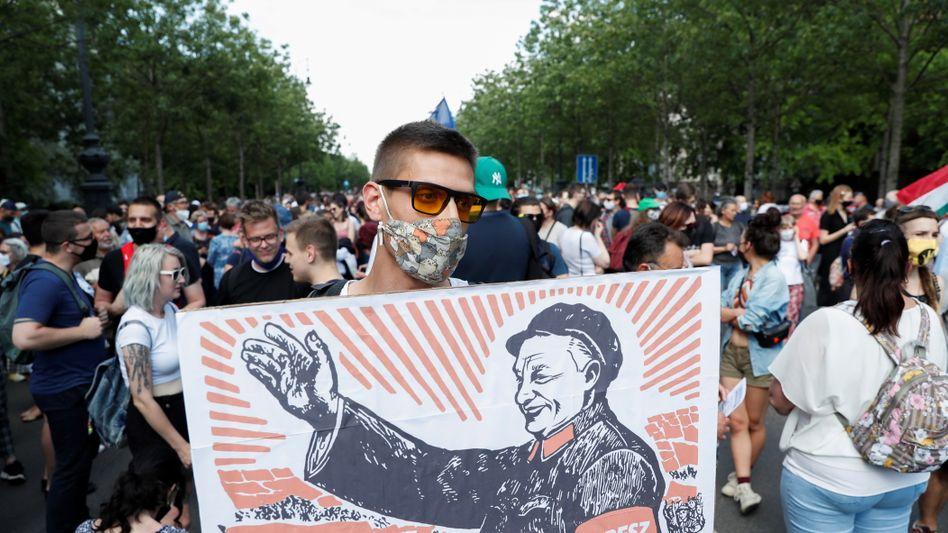 Ein Demonstrant hält ein Plakat mit Viktor Orbán, in der Gestalt von Mao Zedong: »Das Thema Fudan ist der endgültige und vollkommene Selbstmord des Fidesz«