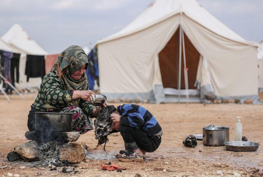 In vielen Camps fehlt es am Allernötigsten: Wie hier bei Ma'arrat Misrin, wo eine Frau die Haare ihres Kindes wäscht