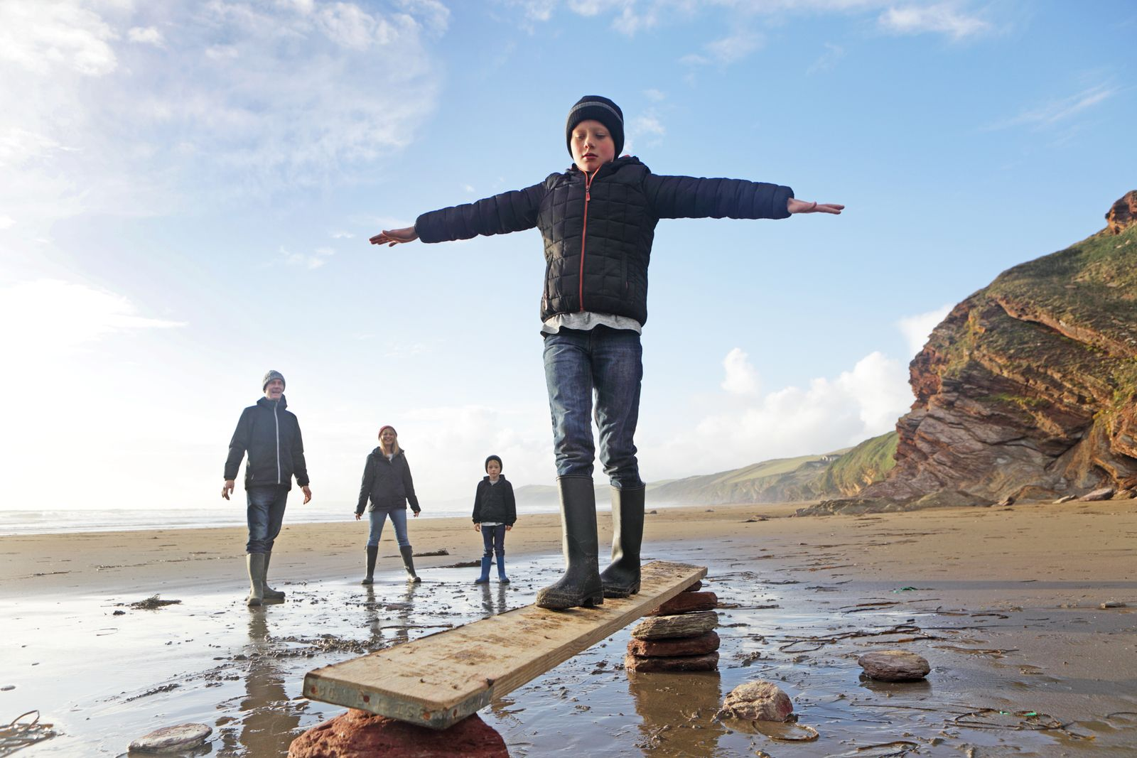Boys balancing on plank of wood, with family on beach