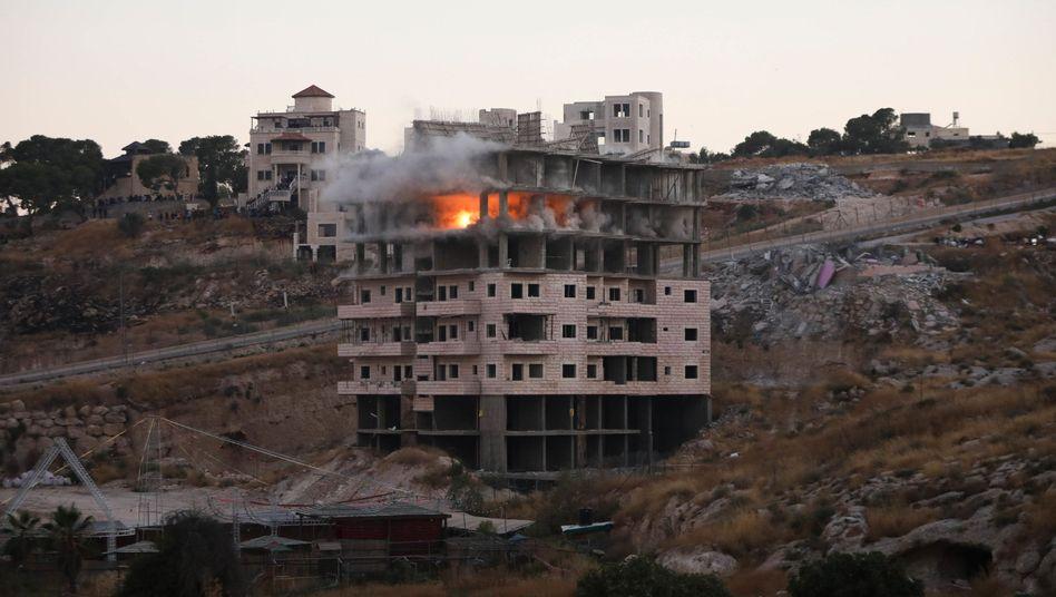 Israelische Streitkräfte sprengen ein Gebäude in einem palästinensischen Dorf - einige der Häuser stehen laut den Friedensverträgen von Oslo unter palästinensischer Kontrolle.
