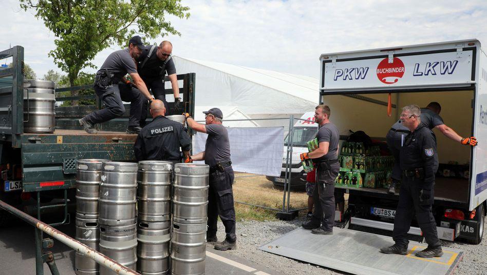 Poizeibeamte stellen Bier auf dem Veranstaltungsgelände beim Rechtsrock-Festival in Themar sicher