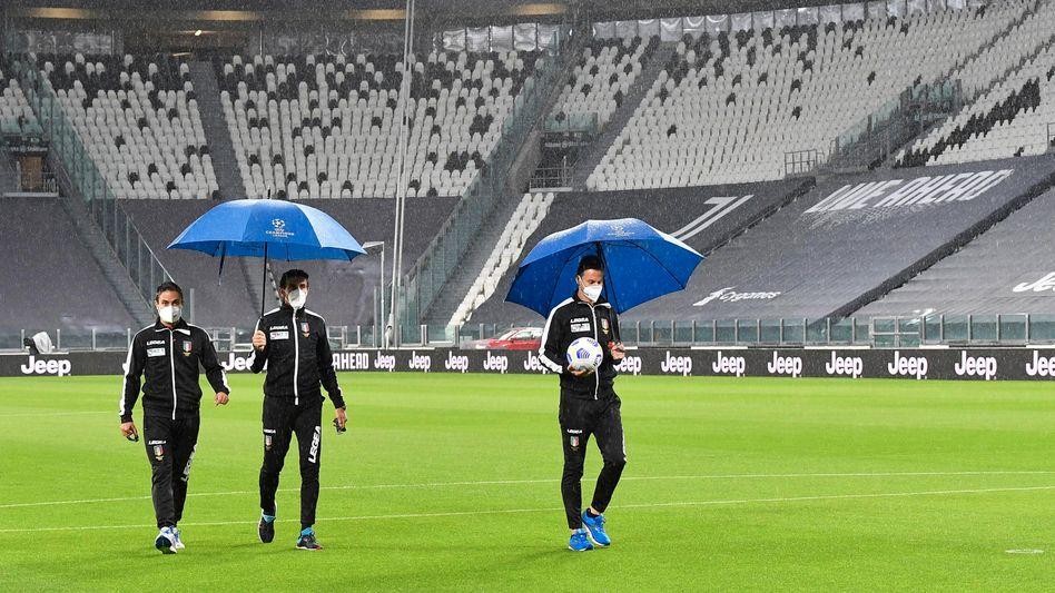 Die Schiedsrichter mit Regenschirm im Oktober auf dem Platz in Turin, aber kein Gegner weit und breit