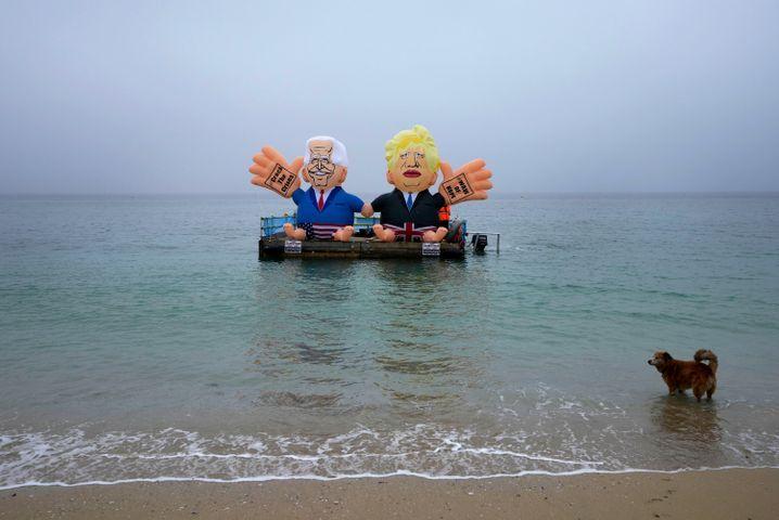 NGOs haben zwei aufgeblasene Figuren, die Joe Biden und Boris Johnson darstellen, auf einem Dock platziert