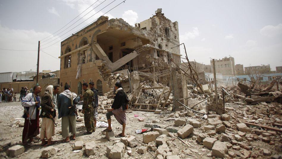 Huthi-Rebellen vor einem zerstörten Haus: Heftige Luftangriffe auf Jemens Hauptstadt Sanaa