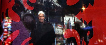 A Kosovo Albanian seen behind an Albanian flag at a market in the regional capital Pristina.
