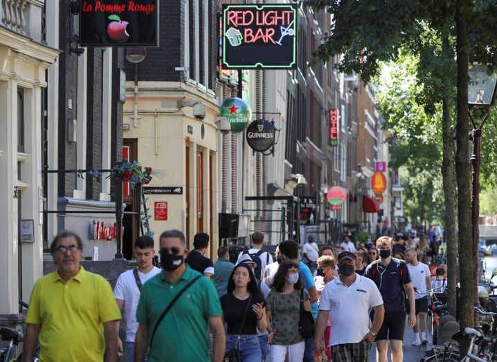 Menschen mit Masken in Amsterdams Rotlichtviertel (Archivbild): über 4000 Neuinfektionen in den Niederlanden in der vergangenen Woche