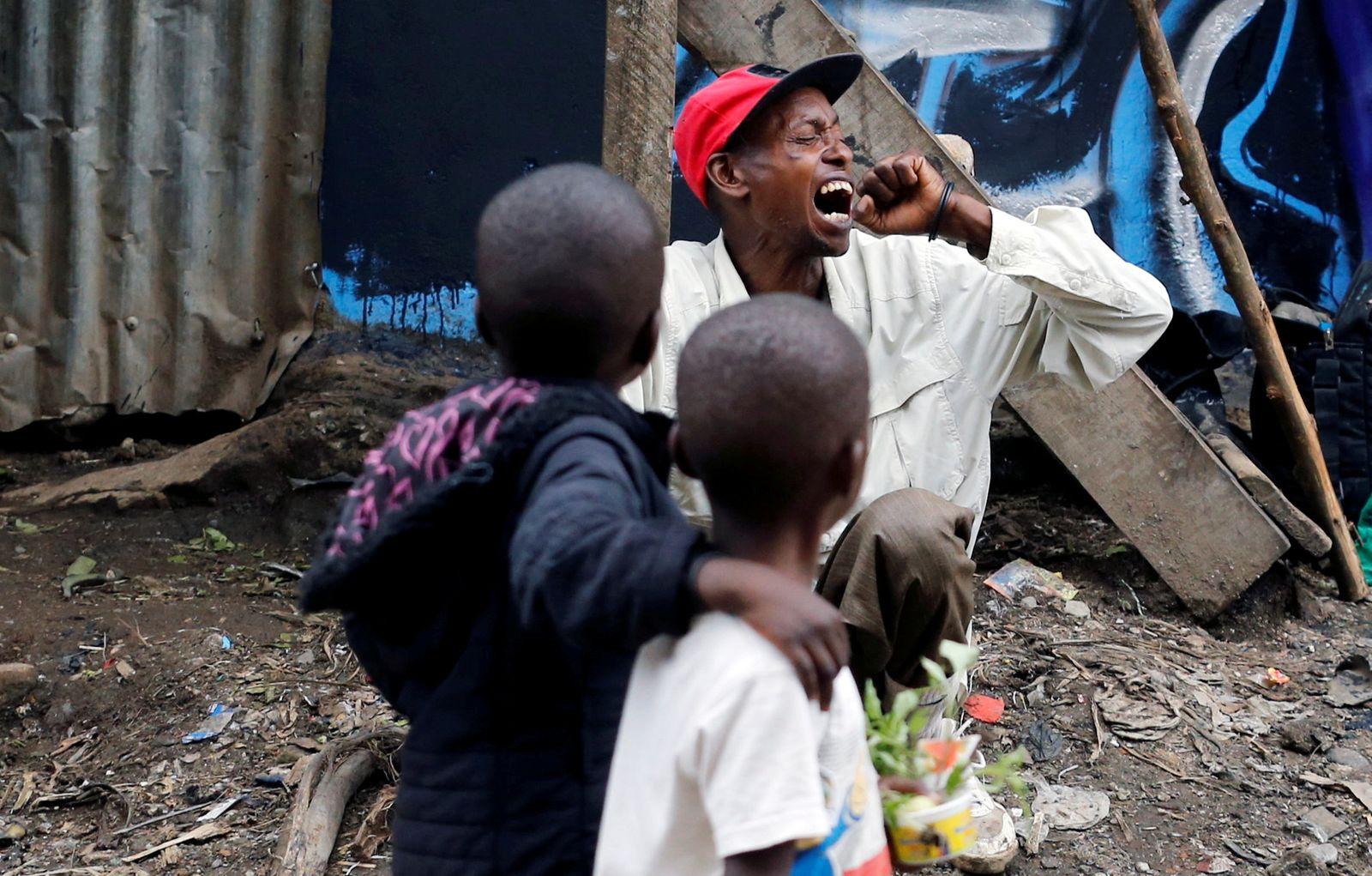 A man coughs as children walk past roadside, amid the spread of the coronavirus disease (COVID-19) in Nairobi