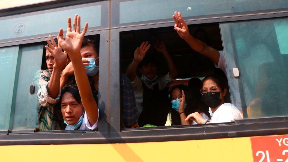Festgenommene Demonstranten winken Menschen, während sie in einem Bus sitzen, der aus dem Insein-Gefängnis kommt