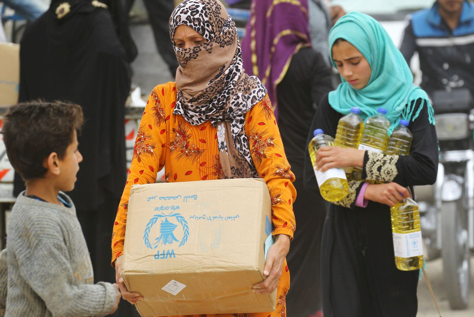FILE PHOTO: Women carry food aid given by UN's World Food Programme in Raqqa