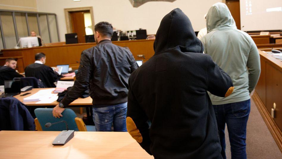 Angeklagte kommen in einen Saal des Landgerichts.