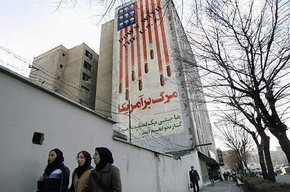 Iranians walk past an anti-US mural in downtown Tehran.