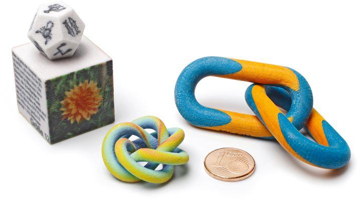 Farbdrucktechniken im Vergleich: Den Würfel und den Dodekaeder links sowie den Regenbogenknoten in der Mitte hat ein 3D-Drucker von 3D Systems aus eingefärbtem Gipspulver aufgebaut. Die gestreiften Kettenglieder rechts hingegen stammen aus einer Maschine von Mcor und bestehen aus farbig bedruckten und verklebten Papierschichten
