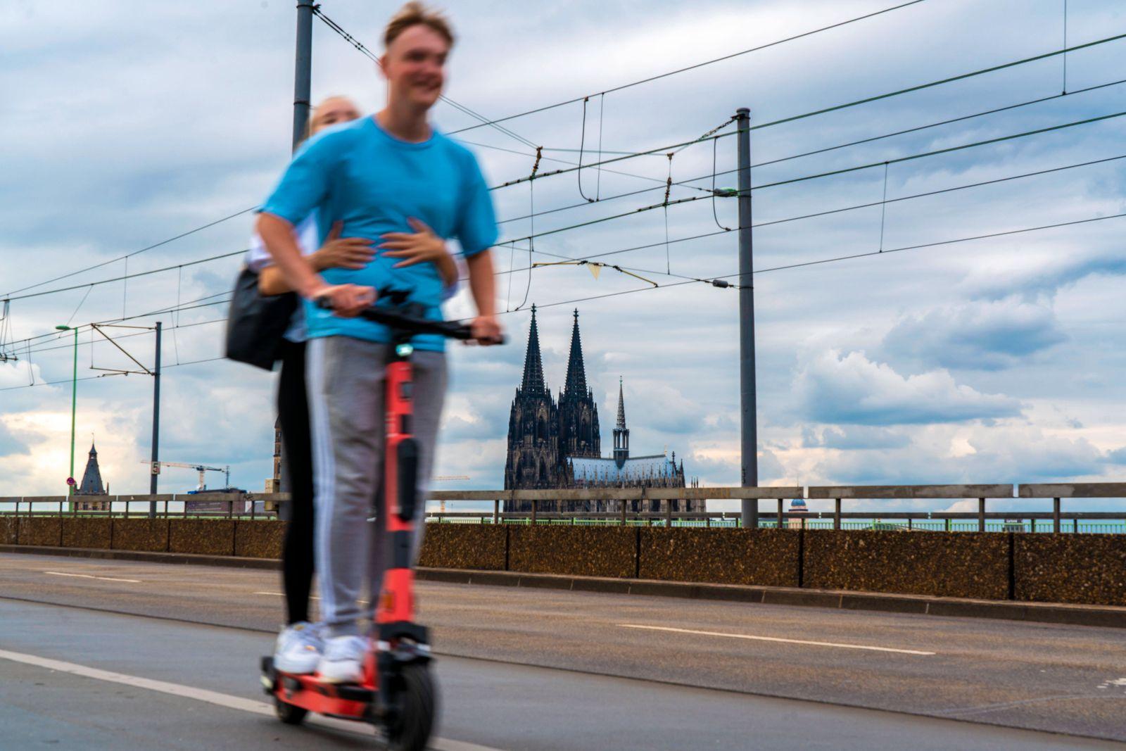 Mobilit?t in der Gro?stadt, E-Scooter Fahrer auf der Deutzer Br¸cke in K?ln, K?lner Dom, Radweg, NRW, Deutschland E-Scoo