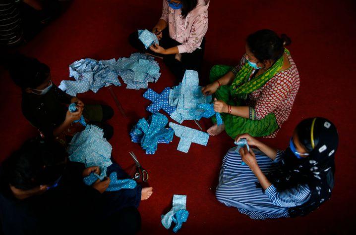 Freiwillige der Mirmirey Youth Society in Nepal stellen Binden her, die sie an arme Frauen verteilen