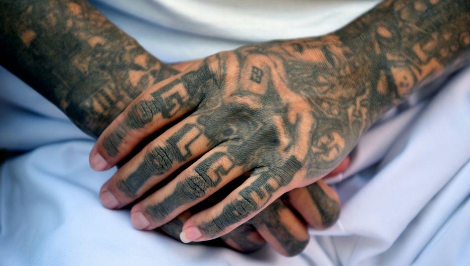 Tätowierungen wie diese sind das Erkennungszeichen von Mitgliedern berüchtigter Gangs, etwa der MS-13 in El Salvador: Die Coronakrise trifft auch illegale Geschäfte