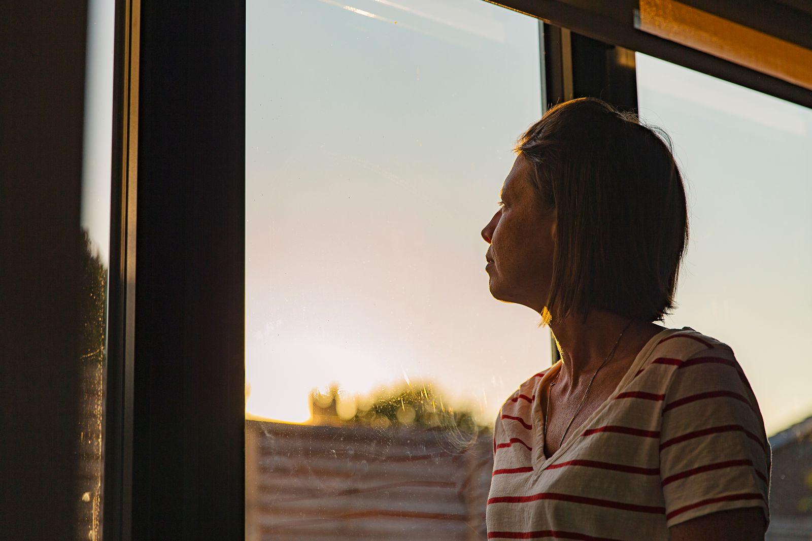 Woman looking through window - negative emotion