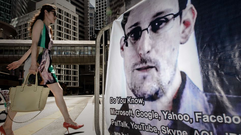 A woman walks past a banner in Hong Kong in support of whistleblower Edward Snowden.