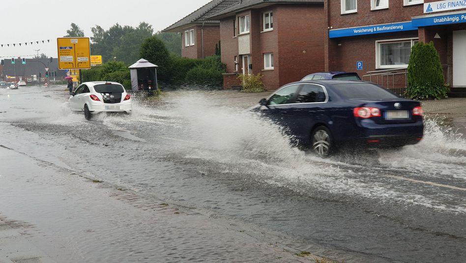 Autos fahren nach Starkregen im Emsland über überflutete Straßen