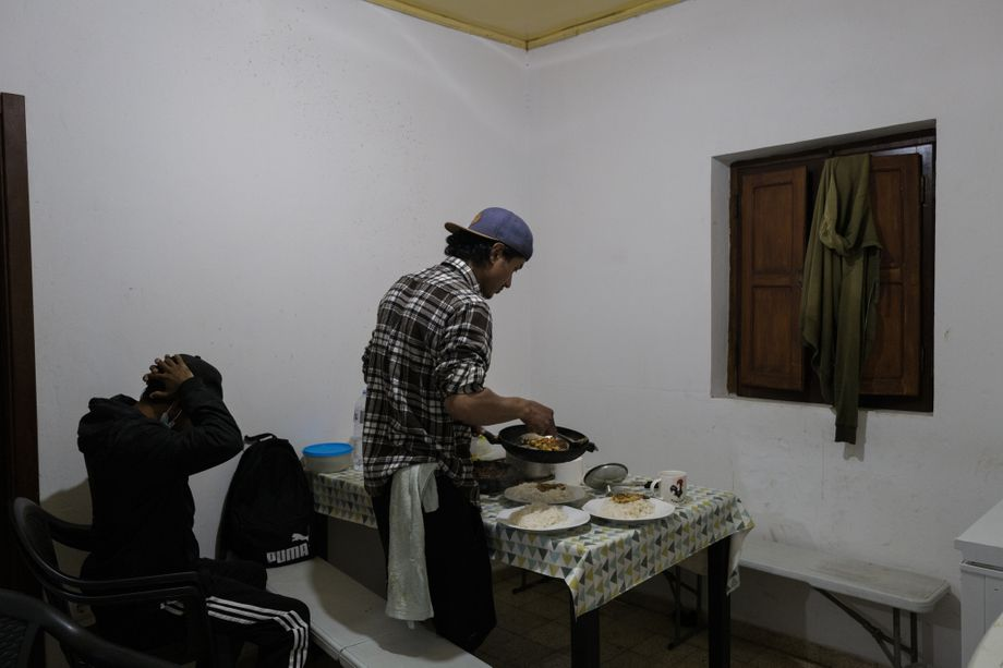 Suraj cooking dinner with his housemate Akash. A total of 18 people live in the run-down house.